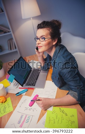 Attractive young woman is working in office - stock photo