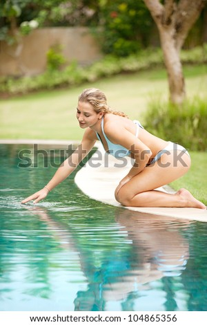 Attractive young woman kneeling by the edge of a swimming pool, touching the calm water with her hand. - stock photo