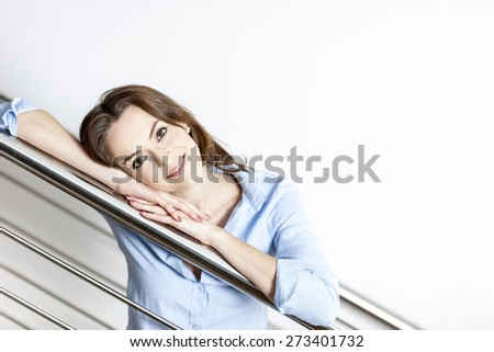 Attractive young woman leaning on a staircase railing smiling