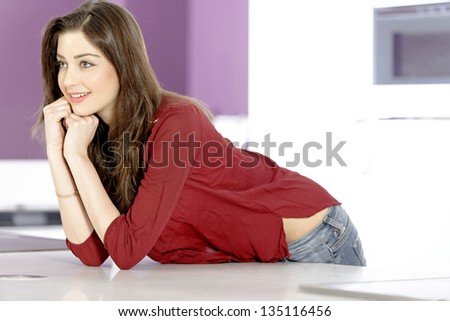 Attractive young woman leaning on her white kitchen work top.