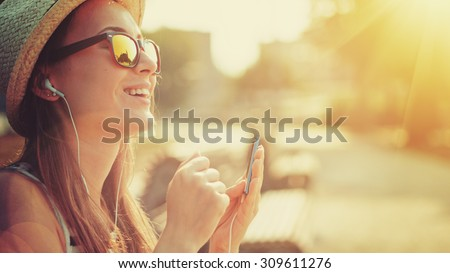 Attractive young woman listening to music on the music player in the city outdoors. Hipster girl enjoying the tunes in her earphones in the morning park. Lens Flare. - stock photo