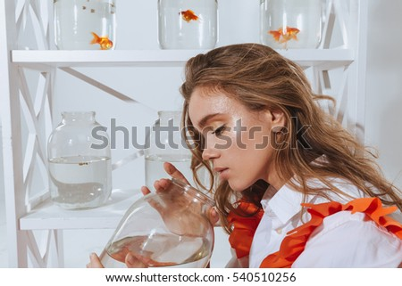 Attractive young woman looking into the jar with gold fish