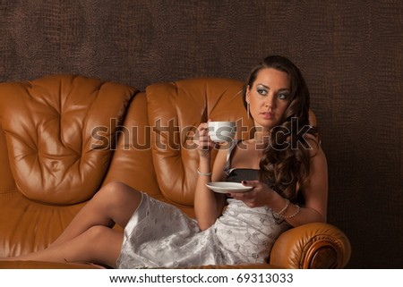 Attractive young woman lying on a leather sofa with cup of coffee. - stock photo