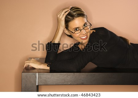 Attractive young woman lying on a table looking over her glasses. Horizontal shot - stock photo