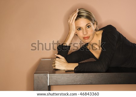 Attractive young woman lying on a table with a sexy smile. Horizontal shot - stock photo