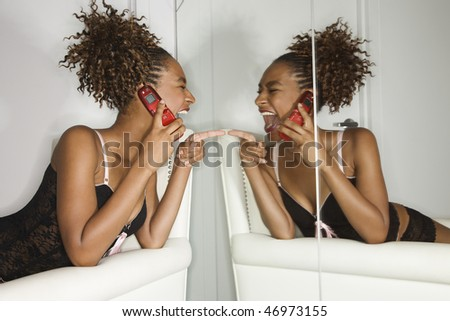 Attractive young woman lying on chaise lounge with a cell phone, laughing and pointing to herself in a mirror. Horizontal shot. - stock photo