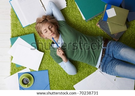 Attractive young woman lying on floor with eyes closed, pen in hand, surrounded by books and notes, relaxing.?