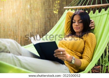 Attractive young woman lying on hammok and reading book outdoors - stock photo