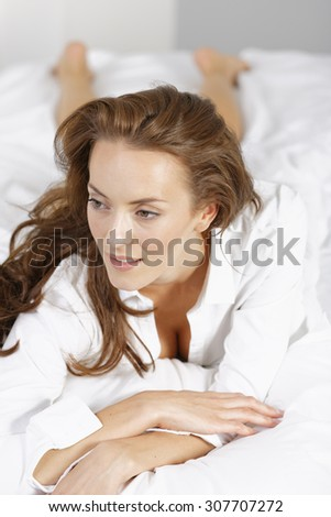 Attractive young woman lying on her bed at home in underwear relaxing and having fun - stock photo