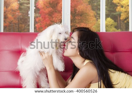 Attractive young woman lying on the sofa while playing and kissing her dog, shot at home - stock photo