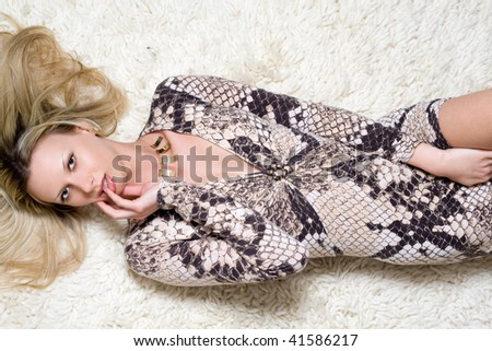 Attractive young woman lying on the white carpet - stock photo