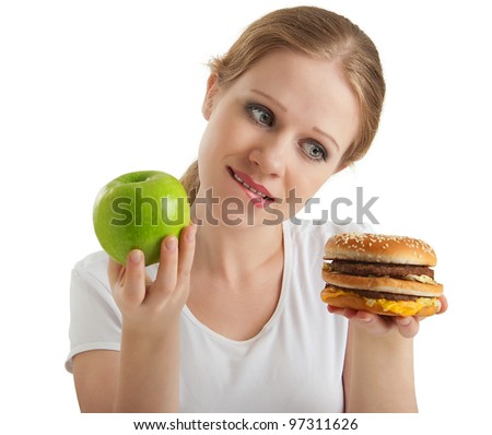 attractive young woman makes a choice between healthy and unhealthy foods, apple and hamburger isolated on white background - stock photo