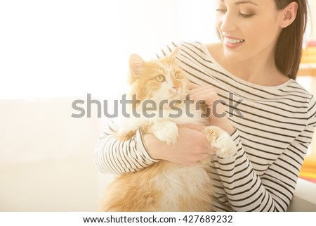 Attractive young woman making fun with animal - stock photo