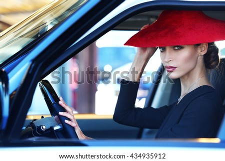 Attractive young woman near the sports car. Beauty, fashion. - stock photo