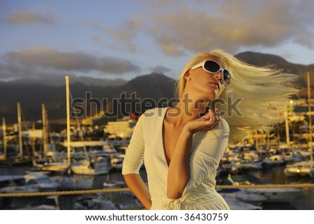 Attractive young woman near the yachts - stock photo