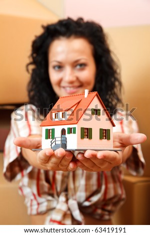 Attractive young woman offering a miniature house, boxes in the background