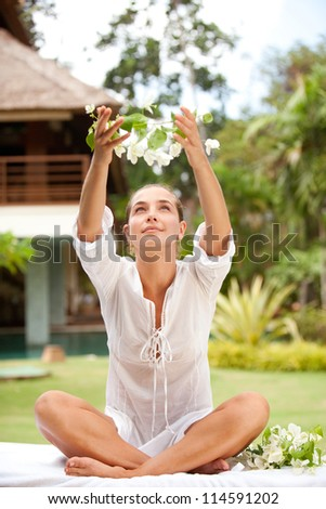Attractive young woman offering and holding tropical flowers in her hands above her head, in an exotic spa garden. - stock photo