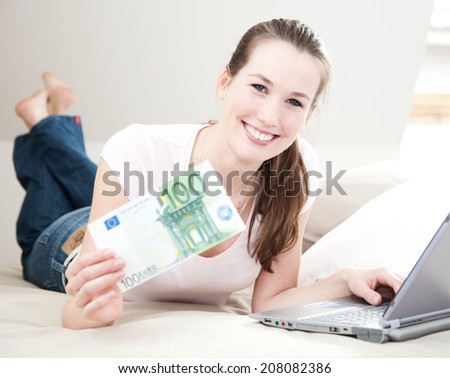 Attractive young woman on her bed with laptop holds 100 euro. - stock photo