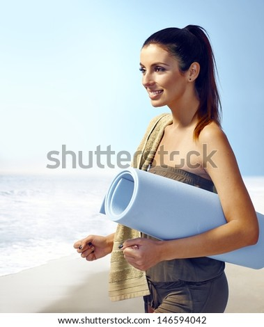 Attractive young woman on the coast, holding beach mattress, smiling happy. - stock photo