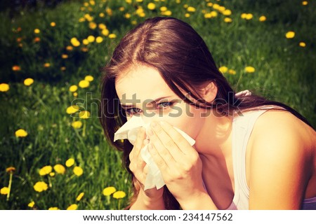 Attractive young woman outdoor with tissue. - stock photo