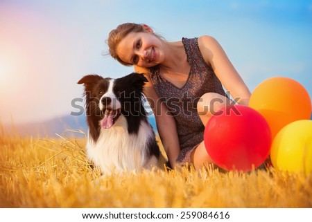Attractive young woman outside in a field holding a dog and balloons. - stock photo