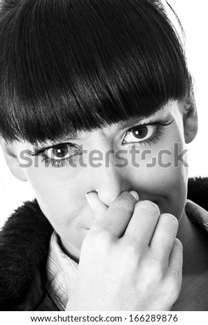 Attractive Young Woman Pinching her Nose - stock photo