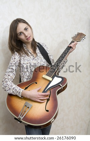 Attractive young woman playing guitar on grey background - stock photo