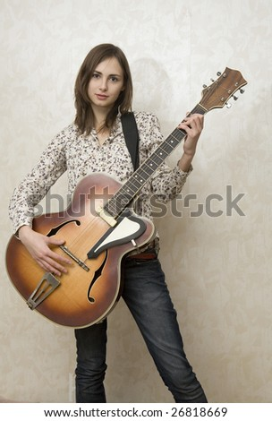 Attractive young woman playing guitar standing at wall - stock photo