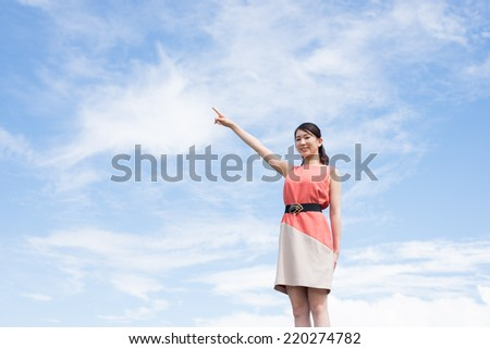 attractive young woman pointing finger on sky background.