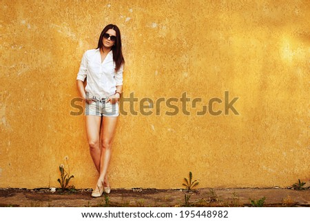 Attractive young woman posing by the wall - stock photo