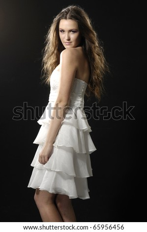 attractive young woman posing in a lovely dress on black background - stock photo
