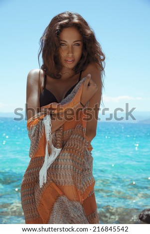 Attractive young woman posing in bikini on a summer day . Shot on the beach. Toned in warm colors.Copy space for text. Vertical, outdoors. - stock photo