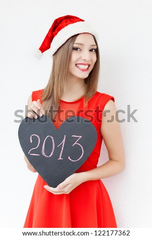 """Attractive young woman posing in red cap on white background with sign New Year """"2013"""". Series. - stock photo"""
