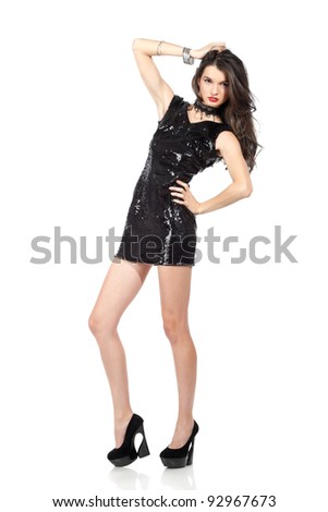 Attractive young woman posing in sequin dress, looking at camera. Studio image, isolated on white background. - stock photo
