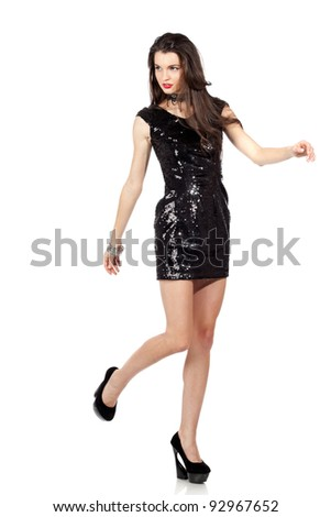 Attractive young woman posing in sequin dress, walking. Studio image, isolated on white background.