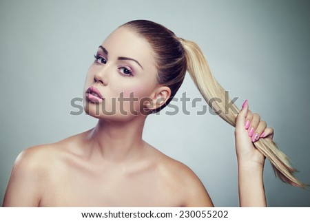 Attractive young woman pulling her hair - fashion makeup - stock photo