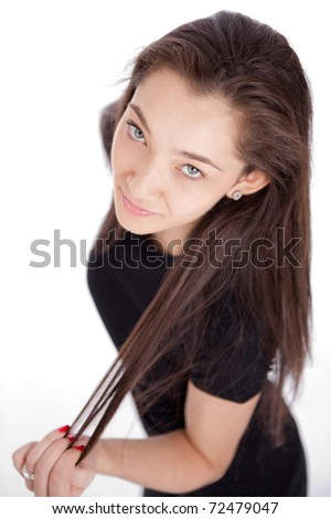 Attractive young woman pulling her long brown hair - stock photo
