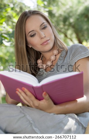 Attractive young woman reading book in park