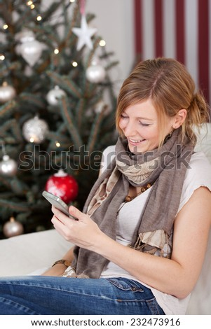 Attractive young woman reading text messages on her mobile phone at Christmas as she relaxes in front of the tree - stock photo