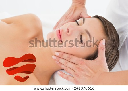 Attractive young woman receiving facial massage at spa center against heart