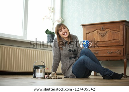 Attractive young woman relaxing at home with cup of tea - stock photo