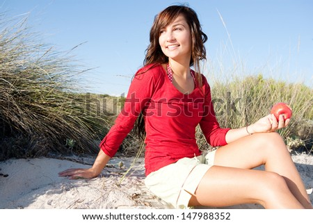 Attractive young woman relaxing on a beach sand dunes while on vacation, holding a red apple and wearing a red shirt, smiling and relaxing during a sunny day. - stock photo