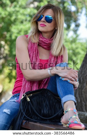 attractive young woman relaxing on the bench outside in the park on summer day  - stock photo