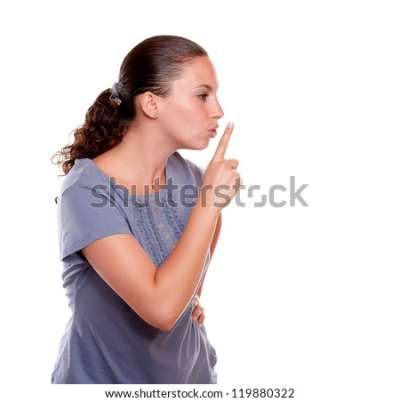 Attractive young woman requesting silence on blue shirt against white background - stock photo
