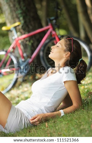 Attractive young woman resting on the grass. Red bike on background