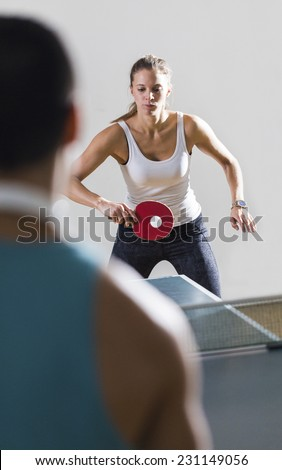 Attractive young woman returning a shot whilst playing an unseen male at table tennis indoors - stock photo