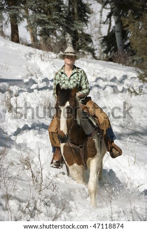 Attractive young woman riding a horse in the snow. Vertical shot. - stock photo