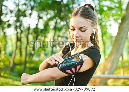 Attractive young woman runner athlete touch her phone in armband during training in evening park with earphones and music at sunset. Pointing, adjusting and looking at gadget display before run - stock photo