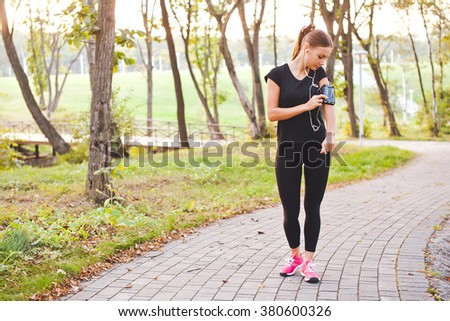 Attractive young woman runner athlete touch her phone in armband during training in evening park on a path with earphones at sunset. Adjust and look at gadget display before run. Full length portrait - stock photo