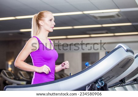 Attractive young woman running on a treadmill, exercise at the fitness club  - stock photo